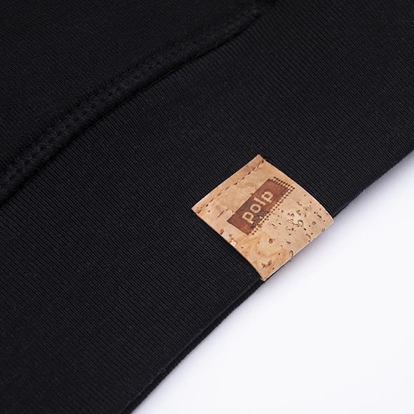 Etiqueta de la marca Polp en sudadera negra, grabado en corcho natural