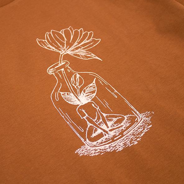 ilustración de una chica con flor en color beige y serigrafiada en camiseta orange