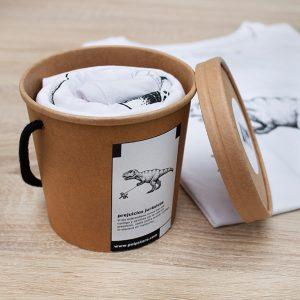 Packaging cubo de cartón reciclado y reutilizable con camiseta blanca de un dinosaurio paseando un caniche